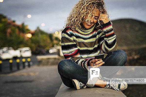 Porträt einer Frau  die einen bunten Pullover trägt und ein Smartphone benutzt  Teneriffa  Spanien
