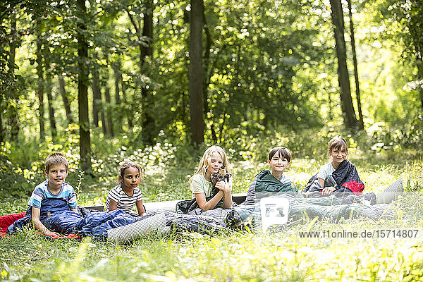 children camping in forest  sitting in their sleeping bags