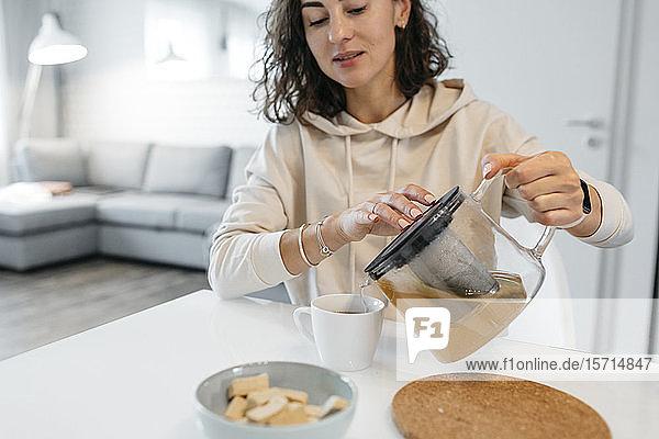 Frau sitzt zu Hause am Tisch und gießt grünen Tee in eine Tasse