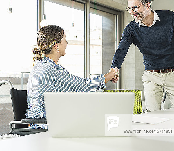 Mature businessman and young businesswoman shaking hands at desk in office