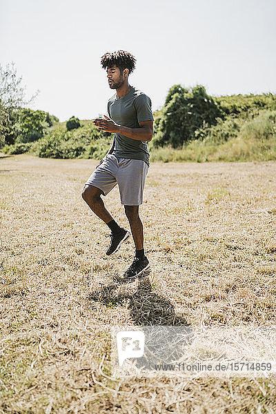 Junger Mann während des Trainings joggt auf der Stelle in einem Park Junger Mann während des Trainings joggt auf der Stelle in einem Park