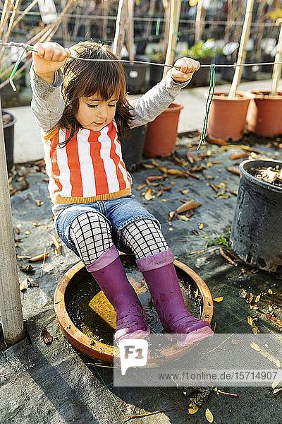 Kleines Mädchen mit Wellington-Stiefeln spielt im Hosenanzug-Kindergarten