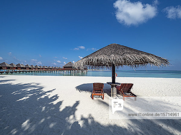 Maldives  Empty deck chairs under straw umbrella on sandy coastal beach in summer