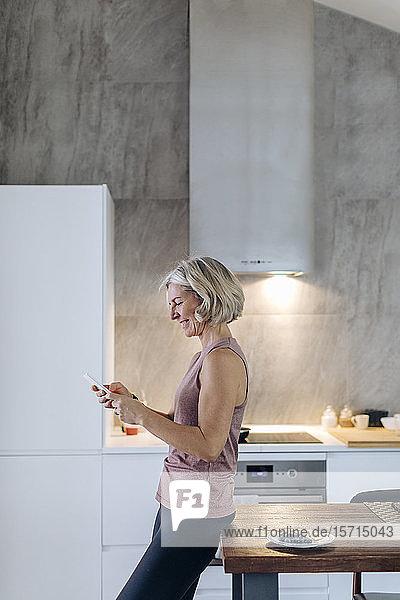 Reife Frau benutzt Mobiltelefon in der Küche zu Hause Reife Frau benutzt Mobiltelefon in der Küche zu Hause