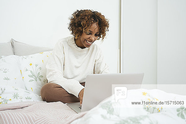 Happy young woman using laptop in bed at home