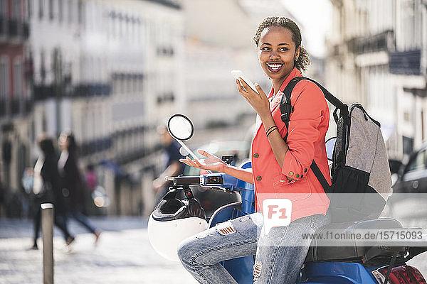 Glückliche junge Frau mit einem Motorroller  die in der Stadt mit ihrem Handy telefoniert  Lissabon  Portugal