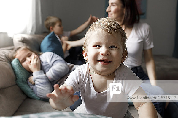 Porträt eines glücklichen kleinen Jungen mit seiner Familie auf der Couch im heimischen Wohnzimmer