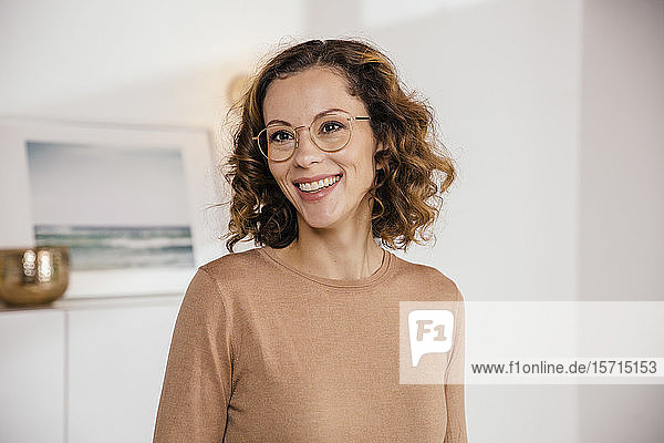 Portrait of smiling brunette woman with glasses at home