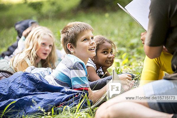 Lehrer liest Schulkindern eine Geschichte vor  Camping im Wald