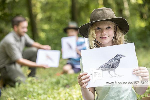 Schulkinder lernen etwas über Tierarten  Mädchen hält Bild eines Vogels