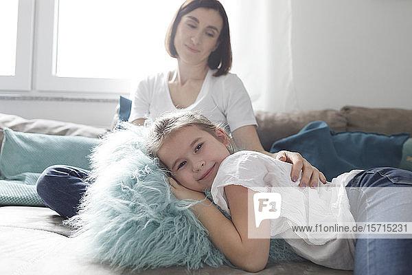 Porträt eines lächelnden Mädchens mit ihrer Mutter auf der Couch im heimischen Wohnzimmer