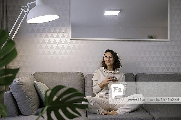 Porträt einer lächelnden Frau  die sich bei einer Tasse Tee auf der Couch zu Hause entspannt