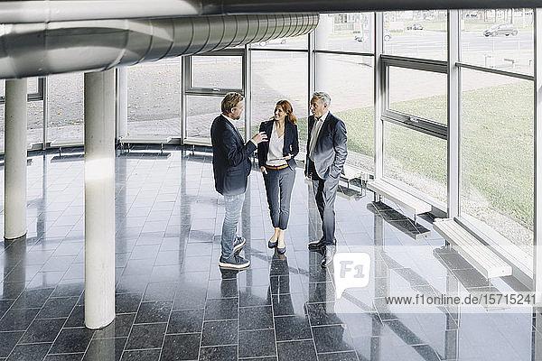 Geschäftsleute sprechen am Fenster in einem modernen Bürogebäude