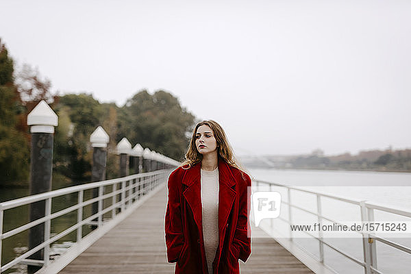 Porträt einer jungen Frau in rotem Mantel auf einer Brücke an einem regnerischen Tag