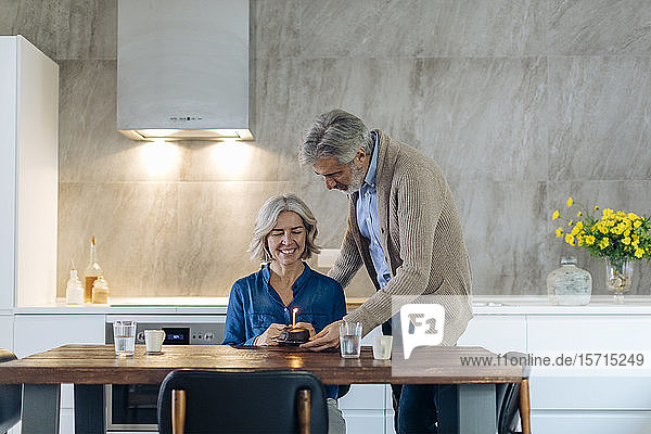 Mature couple celebrating birthday with cake in kitchen at home
