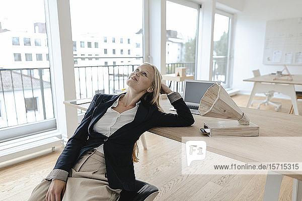 Junge Geschäftsfrau  die sich im Büro auf einen Schreibtisch lehnt und mit einem hölzernen Grammophon Musik hört