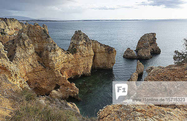 Portugal Faro District  Lagos  Coastal cliffs at dawn with clear line of horizon over Atlantic Ocean in background