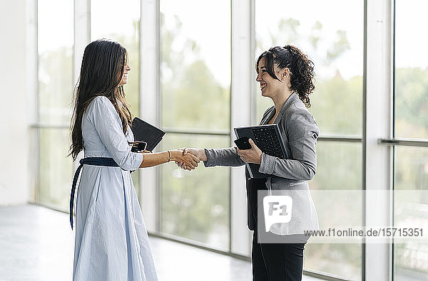 Two happy businesswomen shaking hands at the window