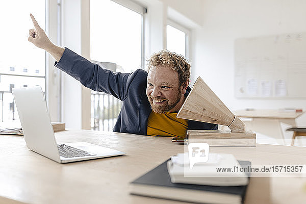 Happy businessman in office listening to music with a wooden gramophone