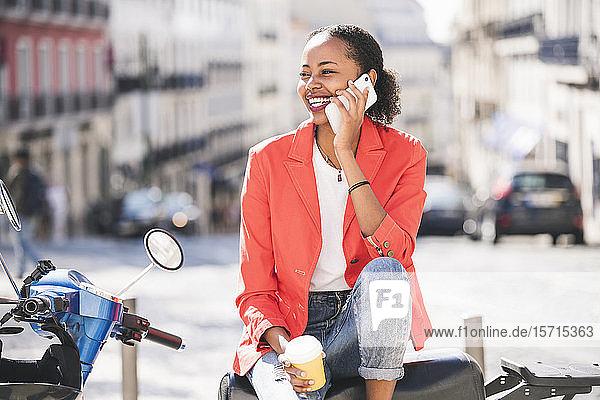 Glückliche junge Frau mit Motorroller telefoniert in der Stadt  Lissabon  Portugal