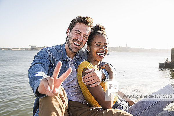 Portrait of happy young couple sitting at the waterfront gesturing  Lisbon  Portugal