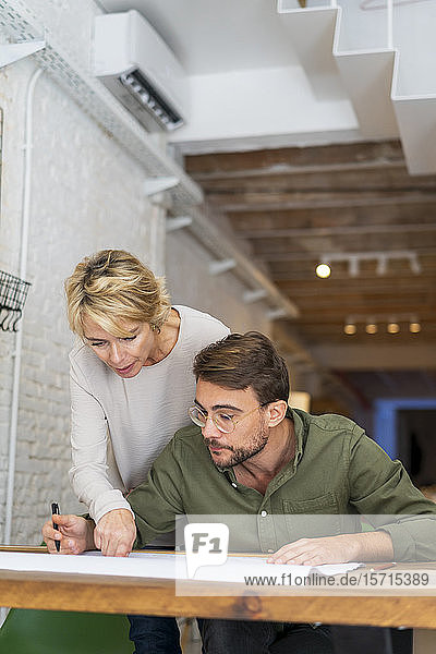 Two architects working together at desk in office