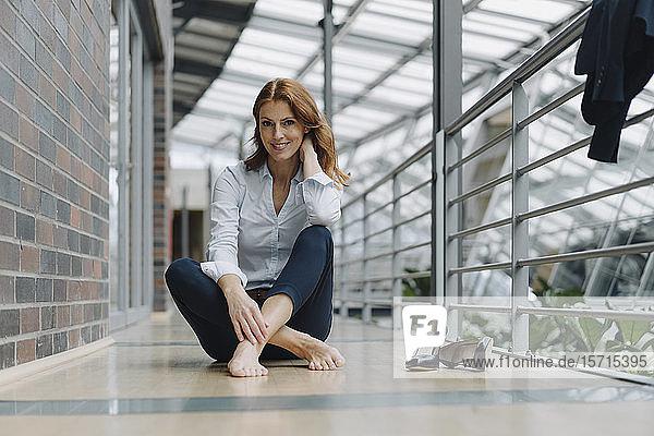 Porträt einer lächelnden Geschäftsfrau  die in einem modernen Büro auf dem Boden sitzt
