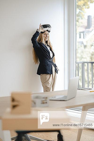 Lächelnde junge Geschäftsfrau mit VR-Brille im Büro