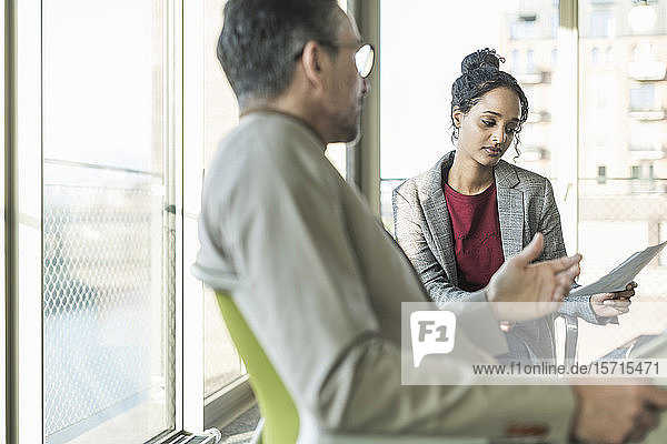 Ein reifer Geschäftsmann im Gespräch mit einer jungen Geschäftsfrau im Amt