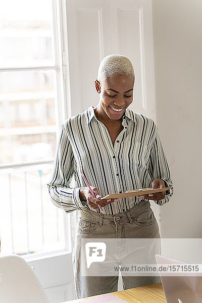 Smiling woman holding clipboard and pencil in office