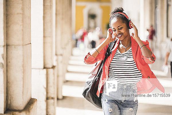 Glückliche junge Frau mit Kopfhörern beim Musikhören in der Stadt  Lissabon  Portugal