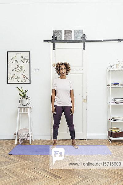 Junge Frau steht zu Hause auf Yogamatte