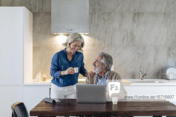 Glückliches reifes Paar mit Laptop auf dem Küchentisch zu Hause
