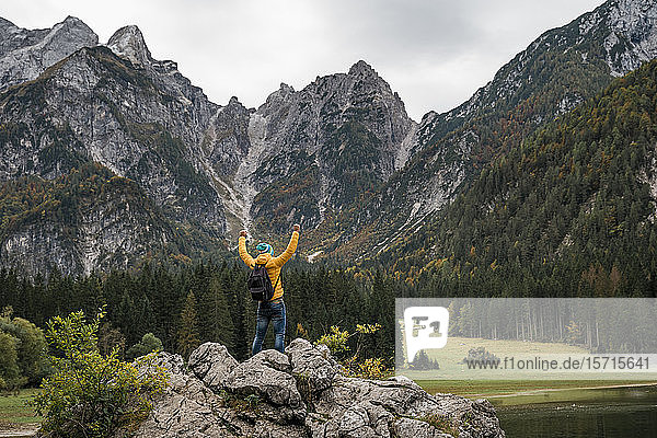 Hiker on viewpoint with raised arms at Laghi di Fusine  Friuli Venezia Giulia  Italy