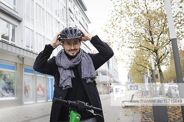 Porträt eines lächelnden jungen Mannes  der mit einem Elektroroller auf dem Bürgersteig steht und einen Fahrradhelm aufsetzt