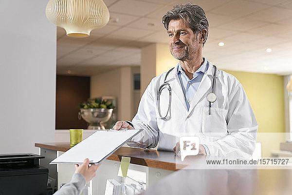 Arzt  der an der Rezeption in seiner Praxis medizinische Aufzeichnungen macht