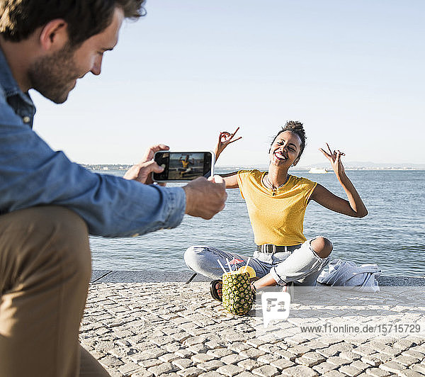 Young man taking a picture of his girlfriend sitting on pier at the waterfront  Lisbon  Portugal