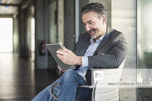 Reifer Geschäftsmann sitzt im Büro auf einem Stuhl und benutzt ein Tablett