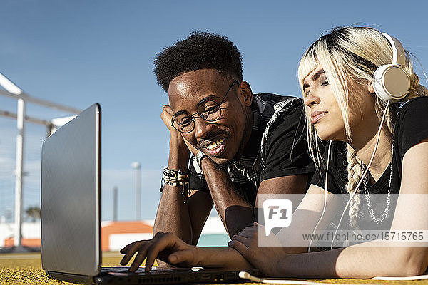 Junges Paar benutzt Kopfhörer und Laptop im Freien