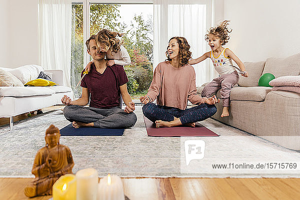 Exuberant girls with parents meditating at home