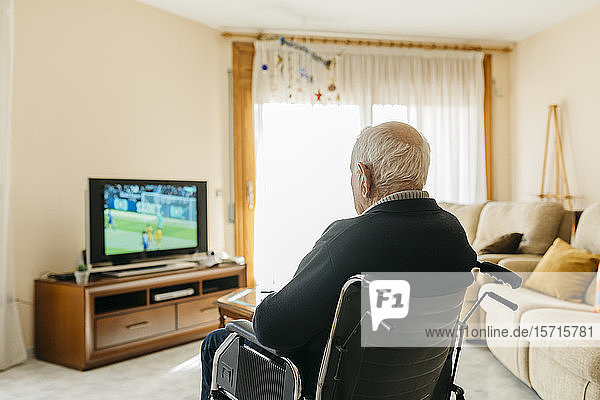 Back view of senior man sitting in wheelchair watching TV at home
