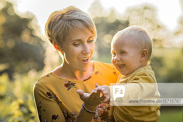 Portrait of happy mother with her little son at backlight