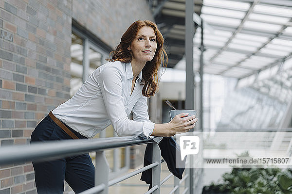 Geschäftsfrau macht eine Pause und isst Müsli in einem modernen Bürogebäude