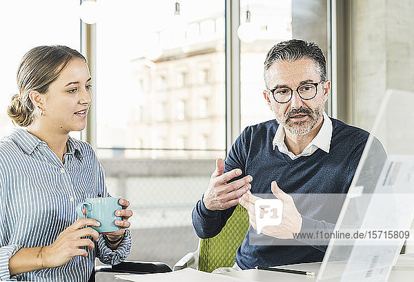 Mature businessman and young businesswoman talking at desk in office