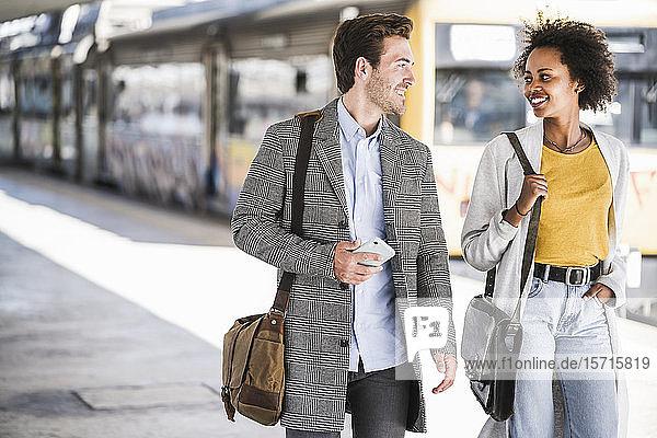 Glücklicher junger Geschäftsmann und Geschäftsfrau  die am Bahnhof spazieren gehen und sich unterhalten