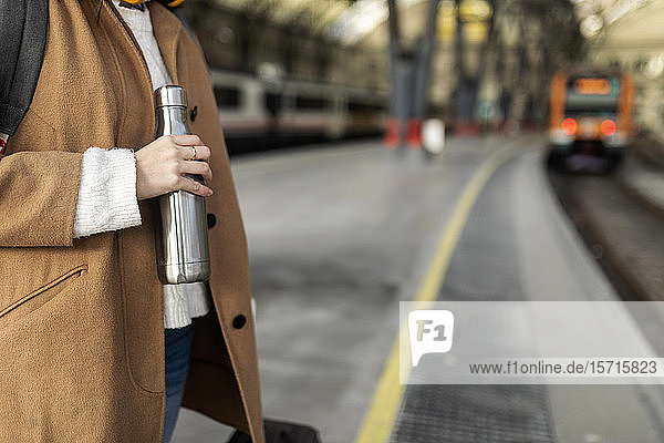 Close-up of woman holding thermos flask at the train station
