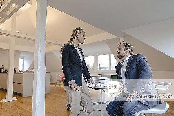 Geschäftsmann und Geschäftsfrau unterhalten sich am Tischtennistisch im Büro