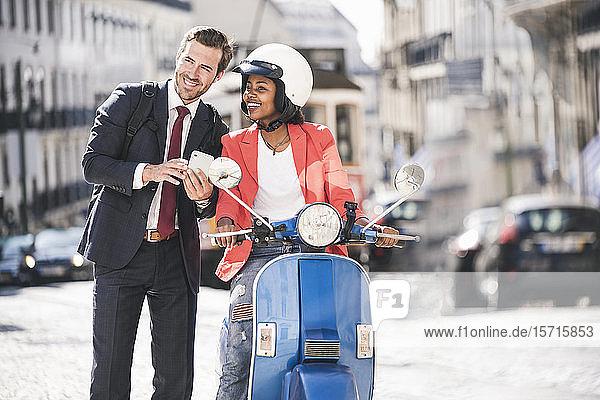 Glückliches junges Geschäftspaar mit Handy und Motorroller in der Stadt  Lissabon  Portugal
