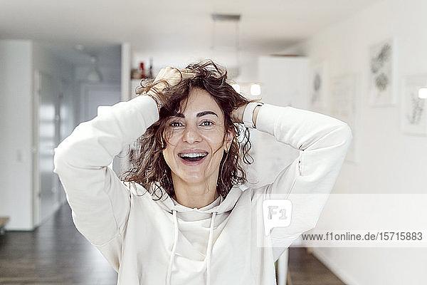 Porträt einer lachenden Frau mit Händen im Haar zu Hause