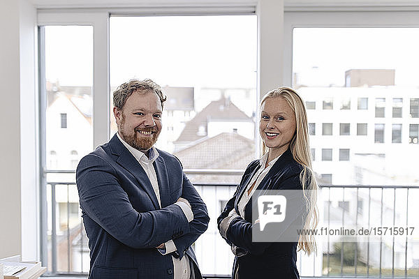 Portrait of confident businessman and businesswoman at the window